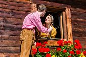 picture of adultery  - Couple in love at mountain hut window wearing traditional clothing - JPG