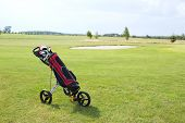 picture of golf bag  - Golf club bag on pushcart at golf course against sky - JPG