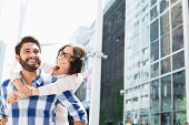 picture of piggyback ride  - Happy man giving piggyback ride to woman in city - JPG