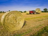 picture of hay bale  - Tractor collecting hay bales in the fields  - JPG