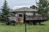 foto of truck farm  - Old rusted farm truck with cloudy blue sky background shallow DOF - JPG