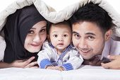 stock photo of muslim kids  - Portrait of happy muslim family with a cute baby looking and smiling on the camera shot under the blanket on bed - JPG