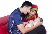 picture of muslim  - Portrait of two muslim parents sitting on sofa while holding their three months baby - JPG