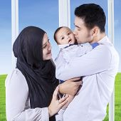 picture of muslim kids  - Two muslim parents carrying and kissing their baby near the window at home - JPG