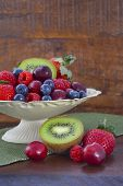 pic of fruit bowl  - Summer Fruit including raspberries strawberries cherries blueberries and kiwi fruit in a vintage bowl with reclaimed dark wood background - JPG