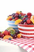 picture of fruit bowl  - Fresh colorful fruit including raspberries strawberries cherries blueberries manadrines and kiwi fruit in breakfast bowls on red check placemat on shabby chic white wood table - JPG