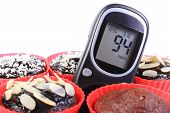 image of diabetes  - Glucose meter and homemade delicious fresh baked chocolate muffins in red silicone cups concept for diabetes and dessert - JPG