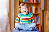picture of daycare  - Funny blond kid boy having fun and smiling indoors - JPG