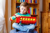 pic of daycare  - Active kid boy playing with wooden toy bus indoors - JPG