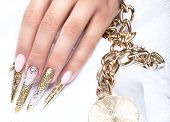 stock photo of long nails  - Beautiful long nails in a gold design with rhinestones - JPG