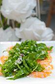 image of rocket salad  - fresh salmon carpaccio sushi sashimi with arugula rocket salad and caper on top - JPG