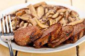 stock photo of deer meat  - venison deer game filet tenderloin and fresh wild mushrooms - JPG