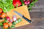 foto of radish  - Fresh organic vegetables and slices of radish and cucumber on a cutting board - JPG
