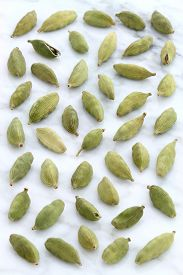 image of cardamom  - beautiful cardamom pods on top of carrara marble coutertop - JPG