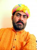 picture of rajasthani  - an indian man in colorful rajasthani turban and long shirt called kurta looking angry - JPG