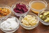 a sampler of fermented food great for gut health - glass bowls against wood:  kimchi, red beets, app poster