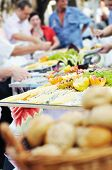 people choosing food from table on catering and buffet party on business seminar conference or weddi
