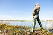 stock photo of fisherwomen  - back view of woman fishing at a pond - JPG