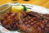 Big thick steak with garnishing corn and gravy