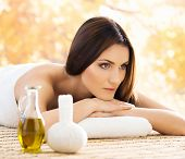 Beautiful, young and healthy woman in spa salon. Massage treatment over yellow autumn background. Tr poster