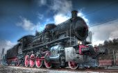 picture of locomotive  - Old Steam Locomotive below cloudy blue sky - JPG