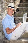 elderly gentleman working outdoors on laptop