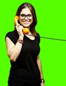 portrait of young woman talking on vintage telephone against a removable chroma key background