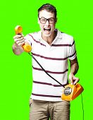portrait of young man holding a vintage telephone over removable chroma key background