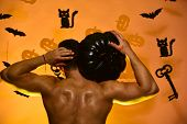 Man With Naked And Muscular Torso Stands On Orange Background. Guy Demonstrates Muscles Turned Back  poster