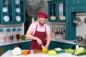 Smiling Chef In Red Apron And Cap At Kitchen Cutting Yellow Paprika For Salad On Cutting Board. Guys poster
