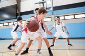 Male High School Basketball Team Dribbling Ball On Court poster