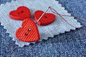 Tiny heart shaped buttons with needle and thread on denim fabric with copy space.  Macro with shallo