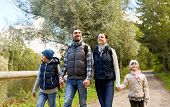 family, tourism and hiking concept - happy mother, father, son and daughter with backpacks walking i poster