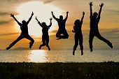 Silhouette Of Friends And Teamwork Jumping On Beach During Sunset Time For Success Business.  Lifest poster