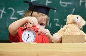 Kid Boy In Academic Cap Near Microscope, Holds Clock In Classroom, Chalkboard On Background. Child O poster