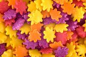 Colourful Sugar Candy Flowers Background, Copy Space. Closeup Of Pile Violet, Yellow And Orange Choc poster