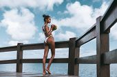 A Svelte Sexy Young Black Girl In A White Swimsuit Is Thoughtfully Looking At The Ocean Horizon Whil poster
