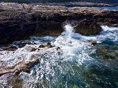 Aerial above waves crashing against coastline rocks poster