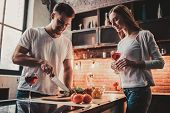 Young Couple Cooking Dinner And Drink Red Wine. Romantic Dinner In Modern Kitchen. Preparing Food On poster