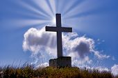 Huge Cross With Sunrays Shining Behind It poster