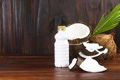 Coconut Milk Bottle With Coconut Half And Coconut Pieces And Leaf  On Wooden Table. poster