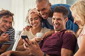 Joyful man showing video on his mobile phone with friends. Group of cheerful young men and women lau poster