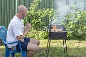 Man Cooking Meat On Barbecue. Young Couple Making Barbecue In Their Garden. Man Cooking Meat On Barb poster