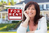 Middle Aged Woman In Front of House with For Rent Real Estate Sign In Yard. poster