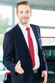 Seller or car salesman in car dealership presenting his new and used cars in the showroom poster