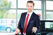 Seller or car salesman in car dealership with key presenting his new and used cars in the showroom poster