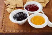 Selection Of Jams With Crisp Biscuits For Tasting On An Old Wooden Board. Blackcurrant Jam, Strawber poster