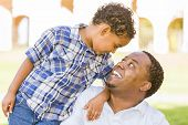 Happy African American Father and Mixed Race Son Playing in the Park.