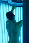 young man closeup at tanning solarium light on