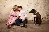 image of queer  - Lesbian kissing couple on floor with pet dog watching - JPG